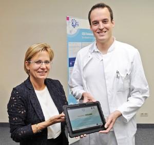 Gesundheitsministerin Barbara Klepsch (CDU) übergibt ein speziell ausgerüstetes Tablet an Dr. Jan Svitil.
